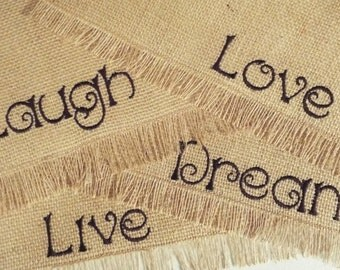 Set of four burlap placemats with the inspiring words live, laugh, love and dream embroidered on each mat.