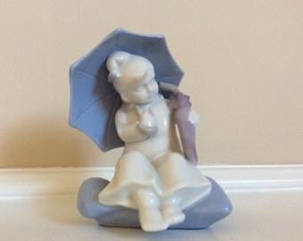Delightful White and Blue Porcelain Figurine of a Girl with an Umbrella over Her Head and Holding a Closed One.