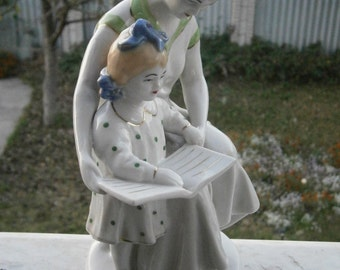 The first book of the USSR Porcelain.The girl sitting beside mom on knees.Soviet statue.