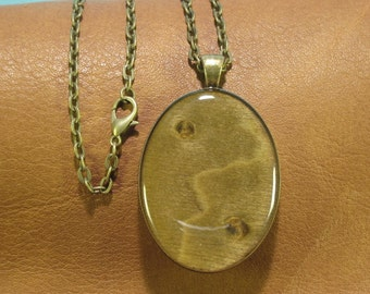 Figured Yellow Poplar wood with pin knots, resin encased in antique brass finish pendant bezel with chain