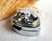 Music box locket, heart shaped locket with music box inside, adorned with wedding rings and flower spray