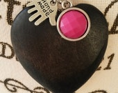 Chain necklace with a black wooden heart pendant and pink cabochon charm