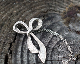 Silver tone ribbon brooch and chain