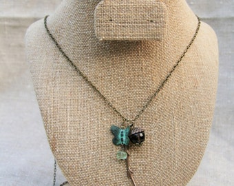Mariposa Necklace: long antique brass chain with smoky quartz acorn, brass branch and patina butterfly with fluorite gemstone dangle