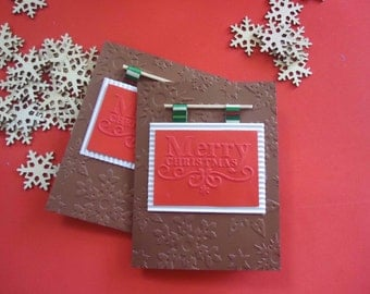 "Christmas Card ""Merry Christmas"" in brown and red tones with reliefs of stars. MErry Christmas Card"