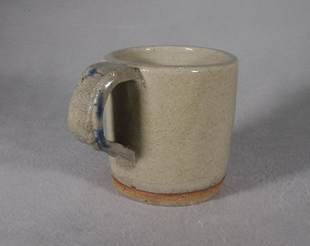 Khaki colored mug with faint floral pattern under the crackle glaze