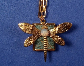 Dragonfly Peace Book, turquoise and gold, holding 14 words for Peace from around the world