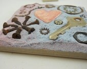 small found object mosaic on 4 inch tile, rusty hardware with a hand crafted ceramic heart in lavender and periwinkle grout