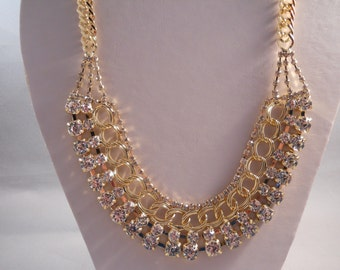 Bib Necklace with a Gold Tone and Clear Rhinestone Pendant on a Gold Tone Chain.