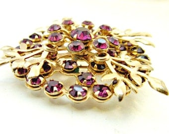 Rhinestone Flower Brooch Purple Glass stone is a gold tone  setting Floral pin