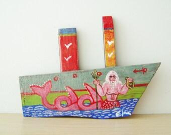 Man mermaid on wooden boat, folk art shabby boat of reclaimed wood, salvaged, old wood folk boat with man-mermaid Poseidon, Greek folk art