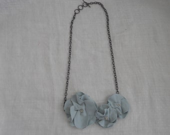 Fabric flower necklace with beaded accents on a metal chain