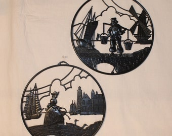 2 Dutch silhouettes with girl tending her ducks, and boy carrying water buckets with ships, windmill, and buildings in the background, 11 in