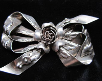 Finely hand crafted bow brooch with intricate flowers heart petals and ribbon detail. Stunning piece to feature with any outfit