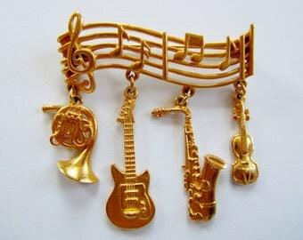 JJ Jonette Gold Tone Sheet Music with Four Dangling Musical Instruments Brooch