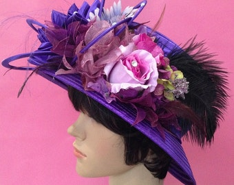 A Violet Fabric Church Hat Decorated With Feather And Flowers.