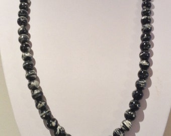 Necklace 59cm Features 10mm round Glass beads. Black with multi white thick  swirly patterns.