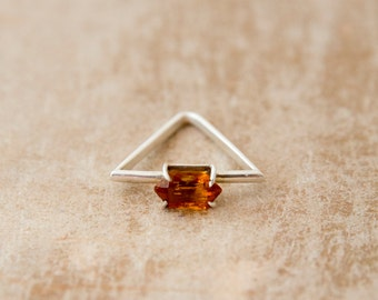 Triangle ring with precious stone.