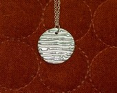 Round pure silver .999 pendant with texture detail on sterling silver chain