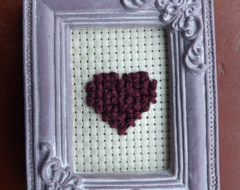 Little cross stitch hearts in rectangular frames.