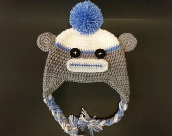 Crocheted blue, grey and white sock monkey hat.