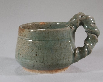 Audacious large jade green stoneware mud with funky twisted handle