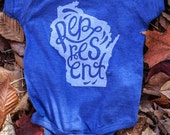 New Represent Wisconsin Blue Baby Onesie. Royal Blue Baby Jumper Celebrates the Midwest. Made in the USA.