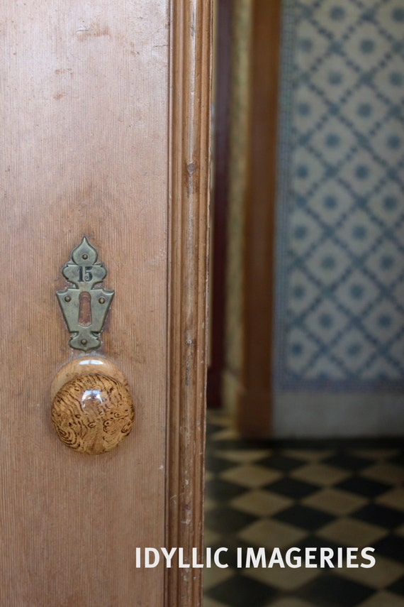 Old open wooden door with a view to antique tiles