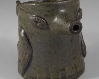Wood ash glazed dark green and brown stoneware javelina jug.