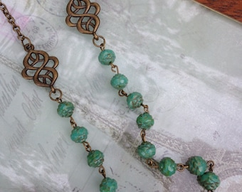 Vintage inspired turquoise blue Picasso Czech glass rosebud beads with antique bronze filigree accents.