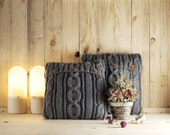 Dark gray cable knit pillow cover with 3 wooden buttons.