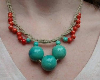 Braided hemp necklace with orange and blue porcelain beads.