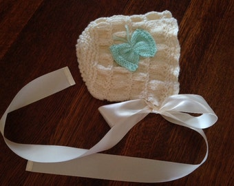 Hand knit baby bonnet with butterfly