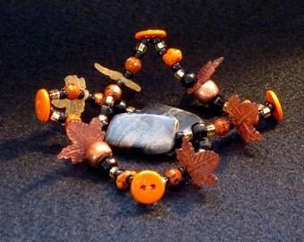 Bright orange to black beads plus autumn leaves stretchy bracelet