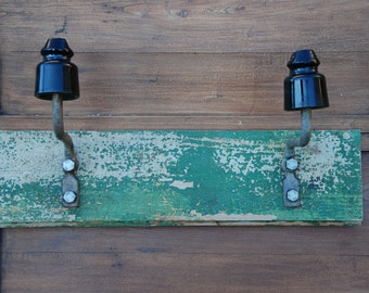 Vintage architectural salvage, electric insulator on old shabby painted board,  wooden coat rack