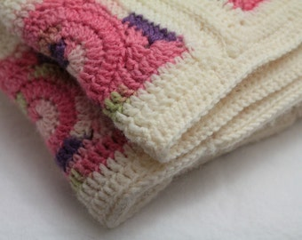 Crocheted pink and off-white wool baby blanket