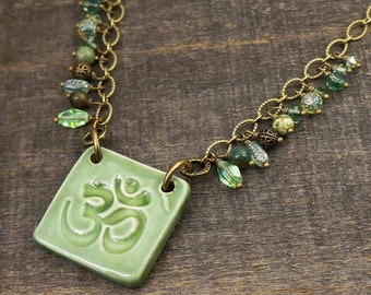 Green Tibetan om necklace, ceramic, vintage glass, semiprecious beads, antiqued brass chain 20 1/2 inches long