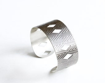 "Wide silver cuff with a geometric pattern and handsawn cut-outs, light patina adds to the modern feel of this striking design - ""Arona Cuff"""