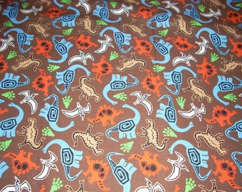 "Dinosaurs - multi color on brown cotton - 43"" wide - sold by the yard"