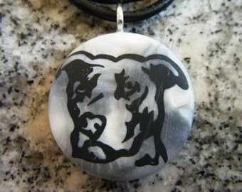 Pitbull hand carved on a polymer clay white/grey pearl color background. Pendant comes with a FREE 3mm necklace