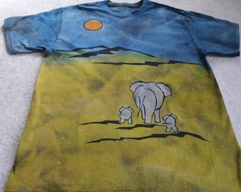 Mama elephant and twins, man's large discharged, dyed shirt, oops, one has wandered off, balboa tree & mountains, brilliant blue,chartreuse