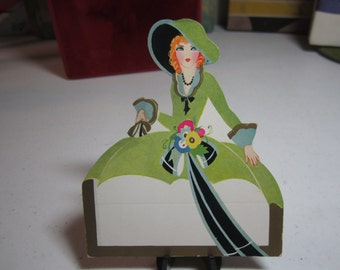 Colorful unused art deco 1930's die cut gold gilded place card of elaborately dressed southern belle large hat walking stick