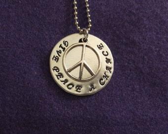 "John Lennon ""Give Peace A Chance"" necklace"