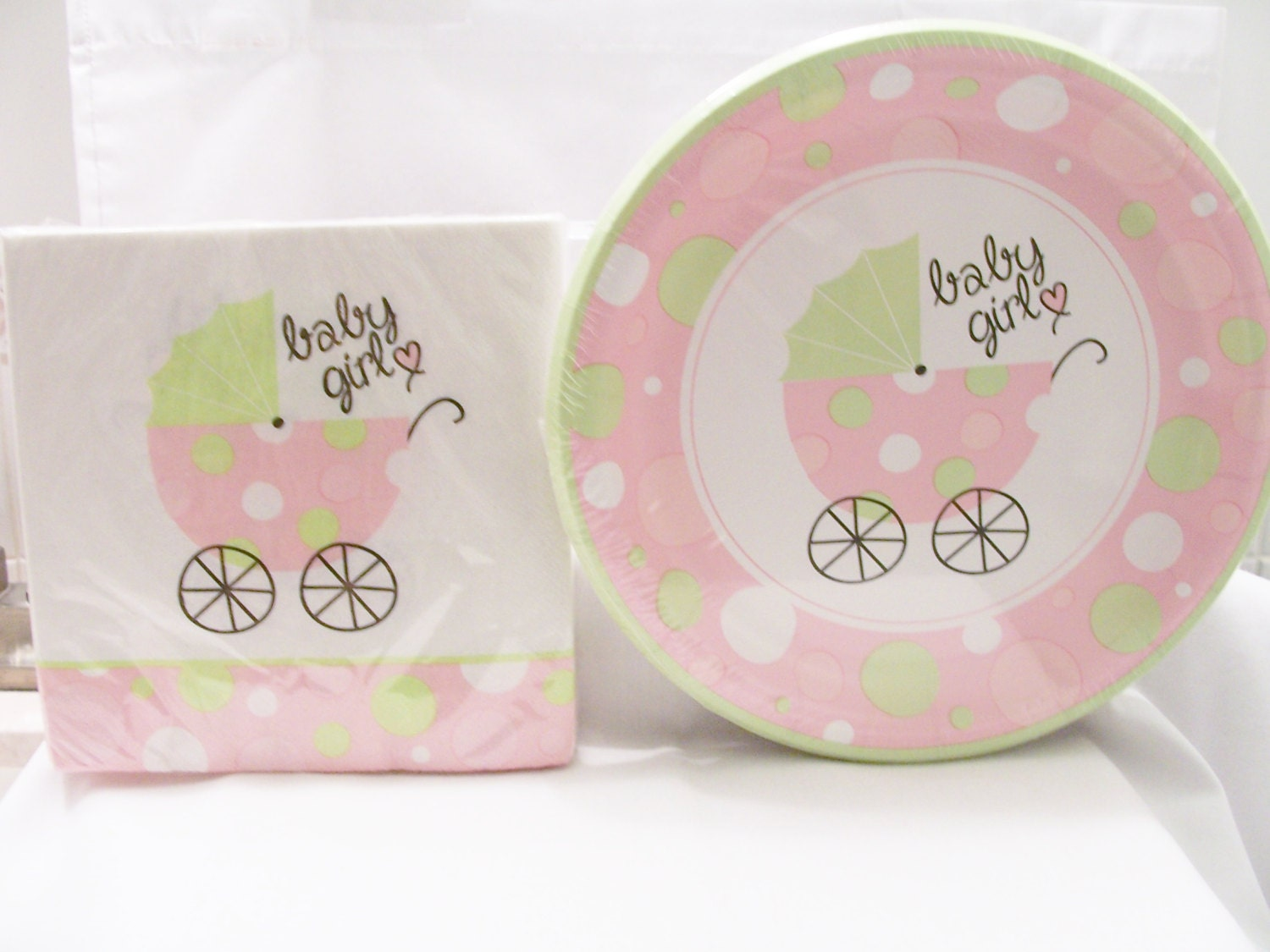set of soft pink and green baby shower paper plates and