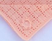 Crochet baby blanket in peach.