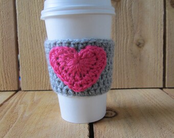Grey crochet coffee cozy with hot pink heart