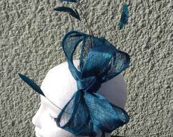 Teal sinamay fascintor made on headband.
