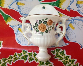 Vintage ceramic urn shaped wall pocket with rose design and gold accents