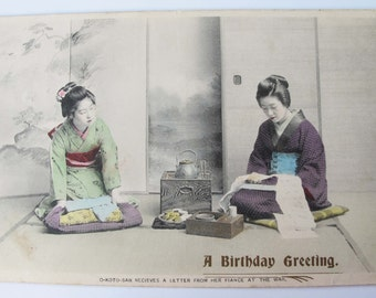 Antique birthday greeting postcard. Hand coloured sepia image of 2 Japanese women. O-Koto-San receives a letter from her fiance at the war.