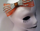 One huge orange skeleton hand hair bow. Portion of sale goes to charity.